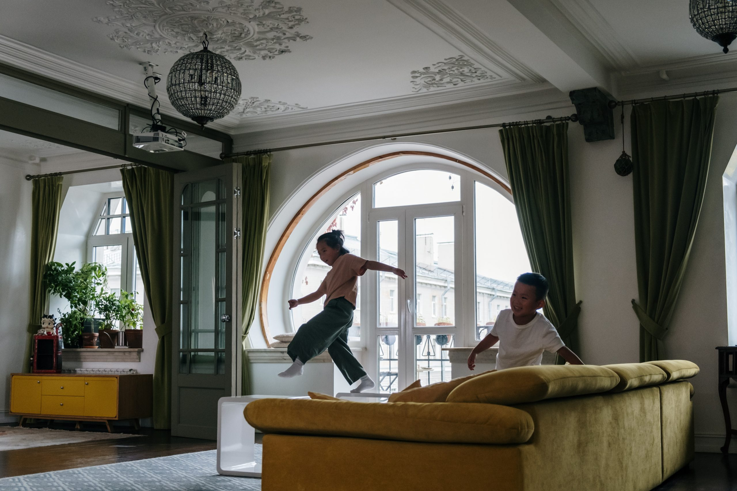 child jumping off the sofa in a living room